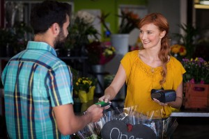 Man making payment with his credit card to female florist